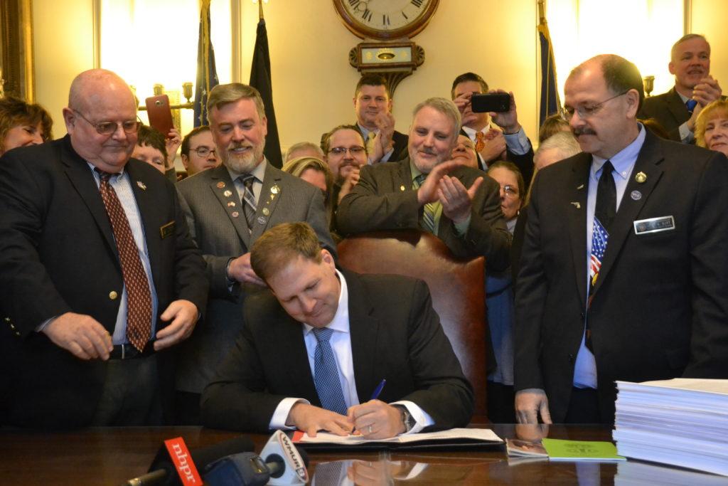 Governor Sununu signing SB 12 looking on is pro-gun State Representative John Burt